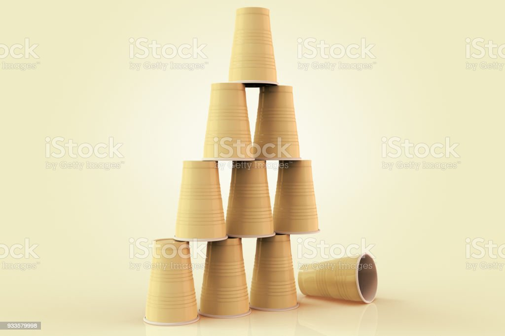 plastic cups stacked in a pyramid with one fallen down representing the concept of failure at teamwork. stock photo