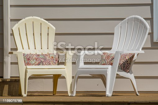 Plastic curveback adirondack chairs on a wooden patio deck