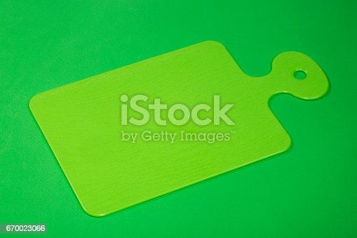 istock Plastic cutting board in green on a green background 670023066