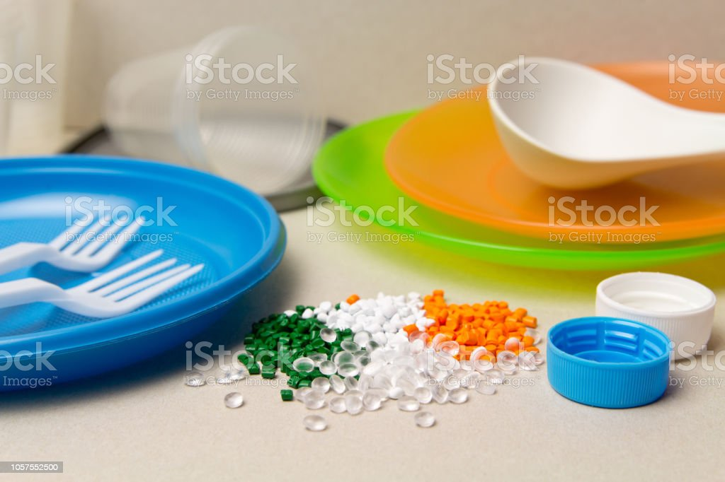 Plastic disposable tableware and Plastic Raw material. Colored granules of polyethylene, polypropylene. BPA FREE concept stock photo