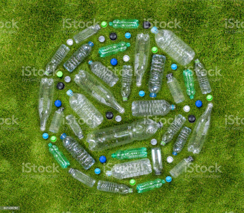 Plastic drinks bottles arranged in a circle on grass stock photo