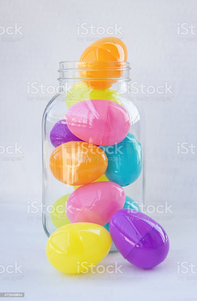 Plastic easter eggs in a clear jar on white stock photo