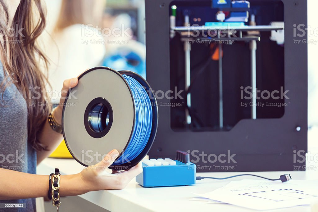 Plastic filament in 3D printer office Close up of female hands holding plastic filaments. 3D printers in the background.  2015 Stock Photo