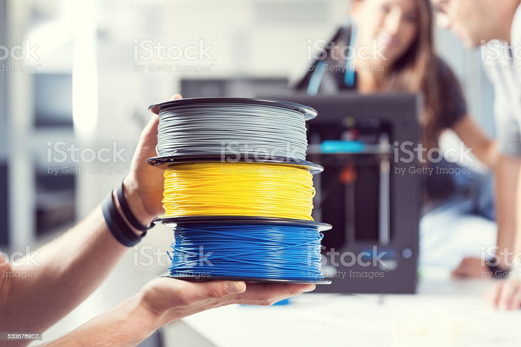 Plastic filaments in 3D printer office Close up of male hands holding plastic filaments. People working on 3D printer in the background.  2015 Stock Photo
