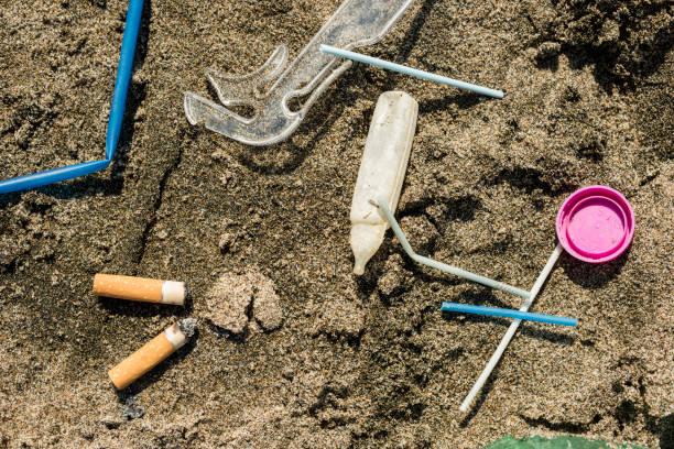 Basura plástica dejó en una playa de arena. - foto de stock