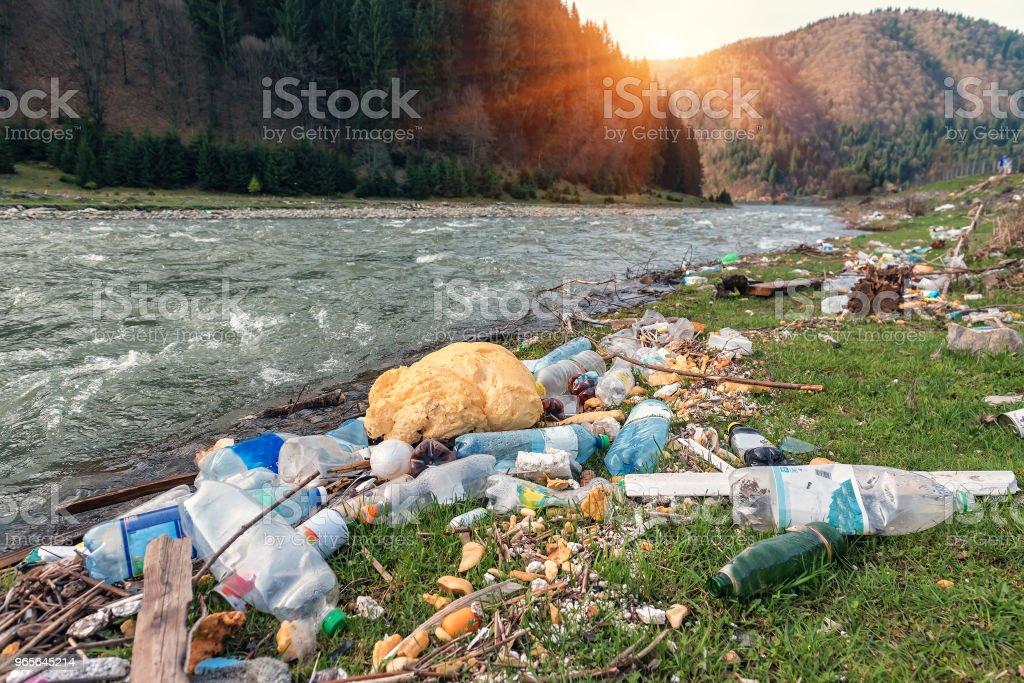 poubelle en plastique sur la rive du fleuve photo libre de droits