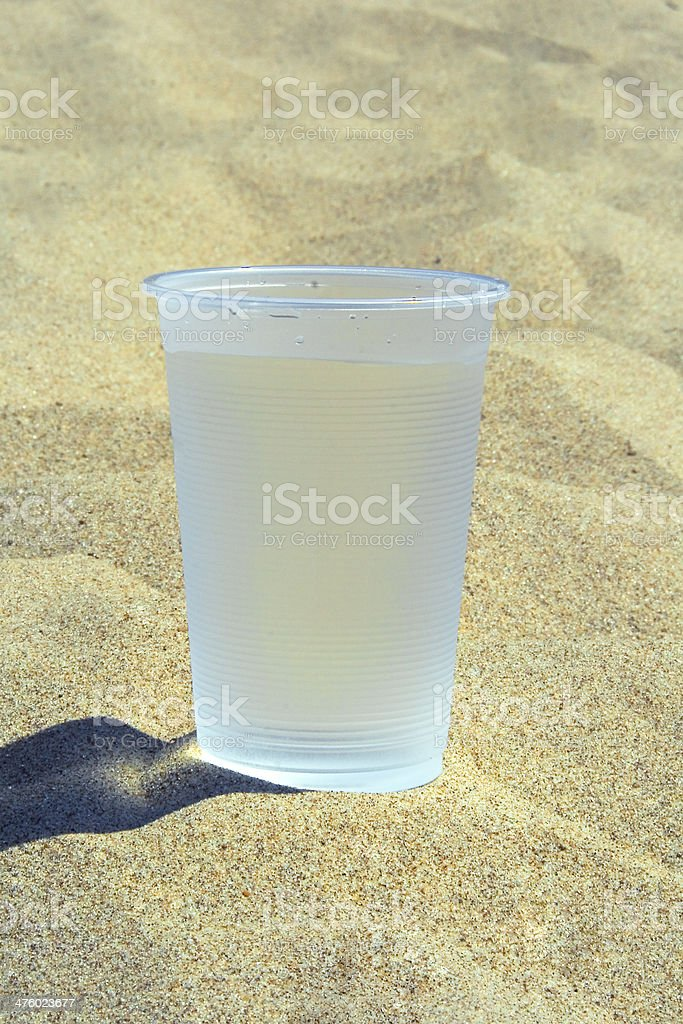 Plastic glass with water standing on the sand royalty-free stock photo