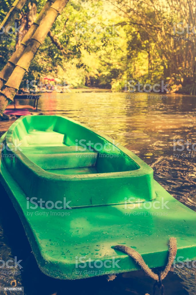 Plastic green boat and calm river with bamboo trees on nature background. stock photo