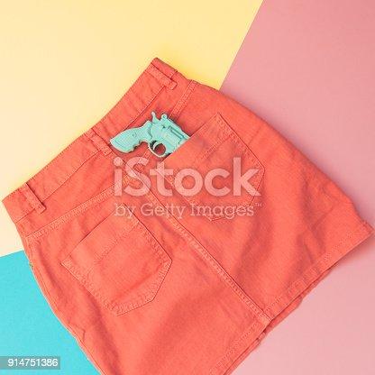 640200626istockphoto plastic gun in the pocket of the orange denim 914751386