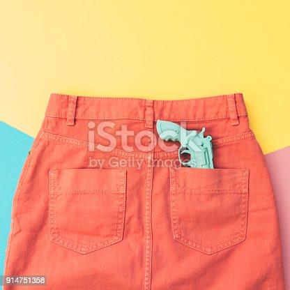 640200626istockphoto plastic gun in the pocket of the orange denim skirt. 914751358