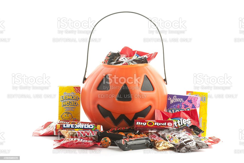 Plastic Halloween pumpkin with trick-or-treat candy white background stock photo