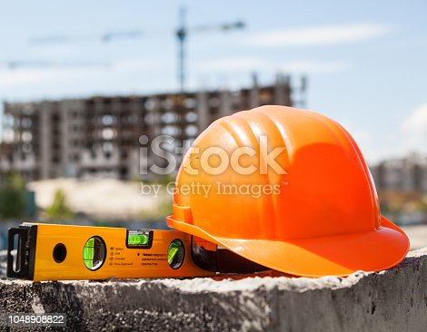 istock Plastic hard hat and spirit level 1048908822