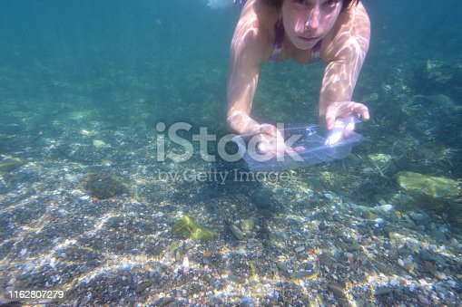 woman picking up garbage, plastic, from the bottom of the sea