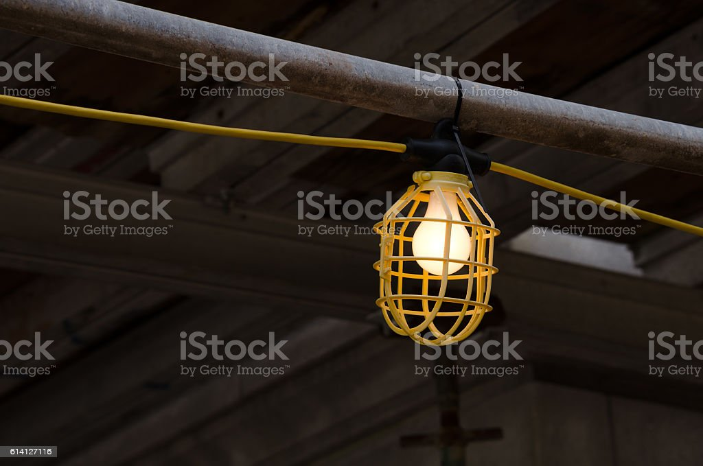 Plastic lamp guard cage with lit lightbulb at construction site – Foto