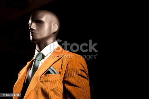 Close up color image depicting a plastic male mannequin behind the glass of a shop window at night. The model is wearing a colorful yellow/orange blazer, waistcoat, shirt and tie. Isolated on black background.