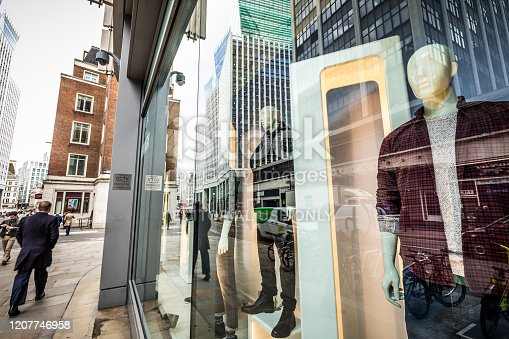 London, UK - 17 February, 2020: color image depicting plastic male mannequins behind the glass of a clothing shop window on a city street in central London, UK. Ultra modern skyscrapers are reflected in the glass, and people are walking by on the sidewalk outside the store.
