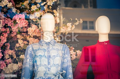 Horizontal color image depicting plastic mannequins wearing colorful floral-patterned womens blouses in a shop window. Behind the dummies is a beautiful fresh flower arrangement. We can see the reflections on the glass of the window. Room for copy space.
