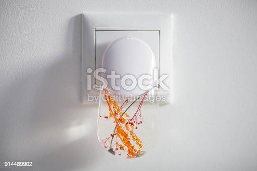 Plastic nightlight illuminating the wall and light switch. Close up