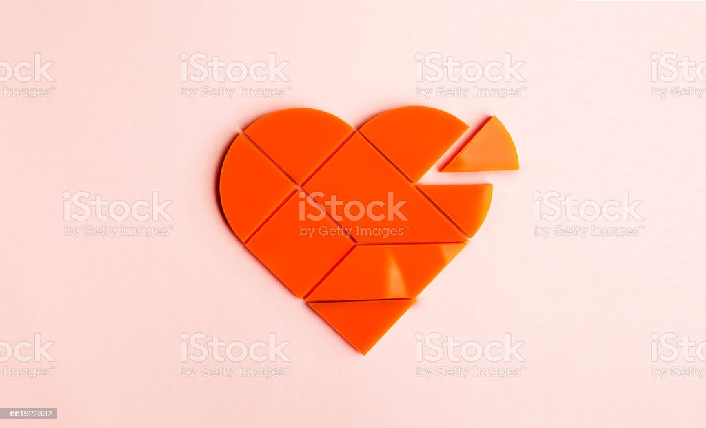 Plastic orange puzzle in the form of a heart with a disconnected piece on a pink background stock photo