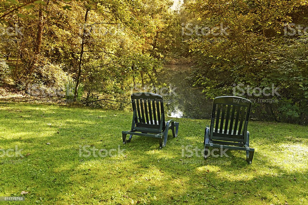 Two plastic lounge chairs in the lawn near the pond surrounded by...