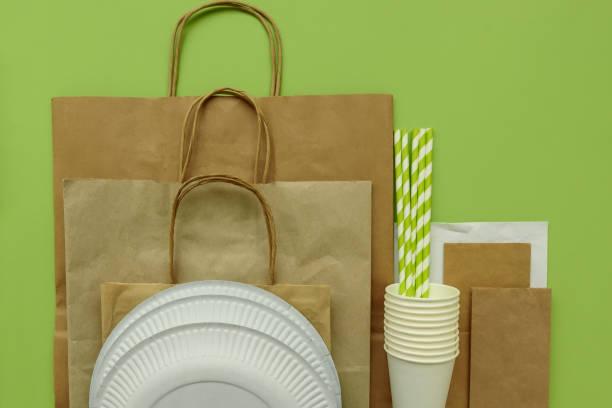 plastikpakete auf grünem hintergrund. platz kopieren. top view. eco, plastisch frei und sparen erde-konzept. - teller kaufen stock-fotos und bilder
