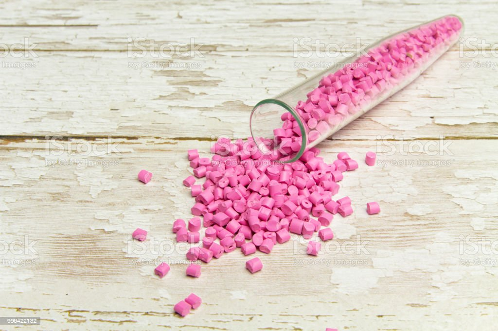 Plastic pallets . Plastic raw materials in granules for industry. Polymeric dye pink on a светлом деревянном background. Plastic granules after processing of waste polyethylene and polypropylene stock photo