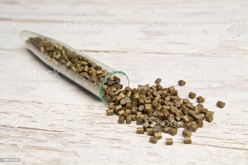 Plastic pallets . Plastic raw materials in granules for industry. The Polymeric dye is Golden on a light wooden background. Plastic granules after processing of waste polyethylene and polypropylene stock photo