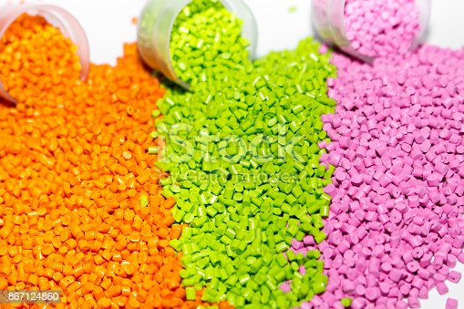 Plastic pellets. Orange green and pink Polypropylene granules scattered on the lab table . Polymeric dye.