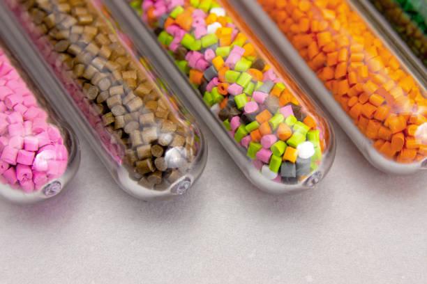 kunststoff-pellets. polymeren farbstoff im reagenzglas auf grauem hintergrund. kunststoff-granulaten nach verarbeitung der abfälle aus polyethylen und polypropylen. polymer. - petrochemische fabrik stock-fotos und bilder