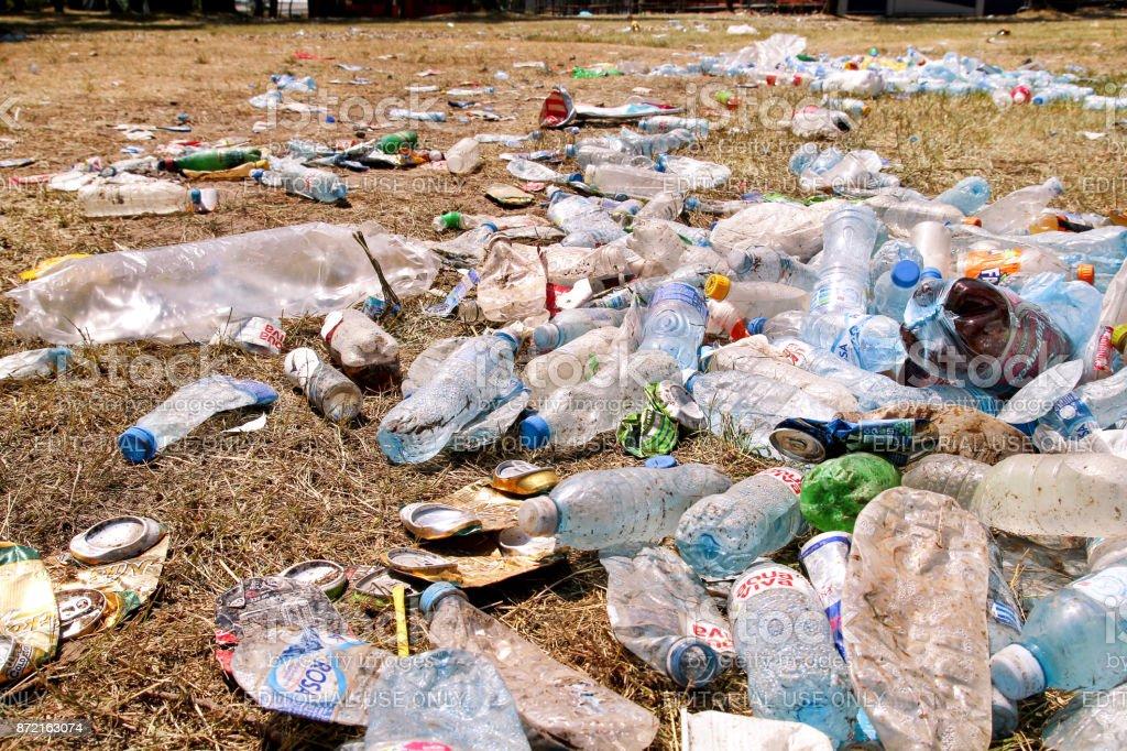 Garrafas de plástico pet deixaram na grama após uma festa, evento. Usado garrafas vazias para o lixo no chão depois de uma festa ao ar livre. Muitos lixo, lixo, bin, sacos de plástico. - foto de acervo