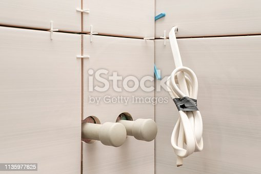 plastic pipes with plugs and electrical cable protruding from the wall with ceramic tiles
