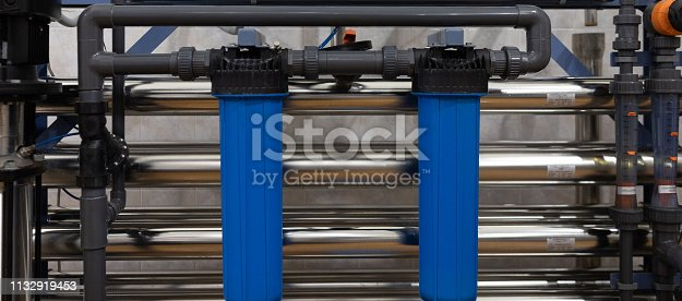1132919442istockphoto Plastic piping with blue holders. industrial background 1132919453