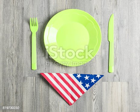 470765518 istock photo Plastic Plate, Fork, Knife,Napkin And American Flag  On Table 519730232