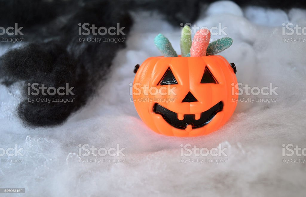 Plastic pumpkin buckets with candy on black and white smoke royalty-free stock photo