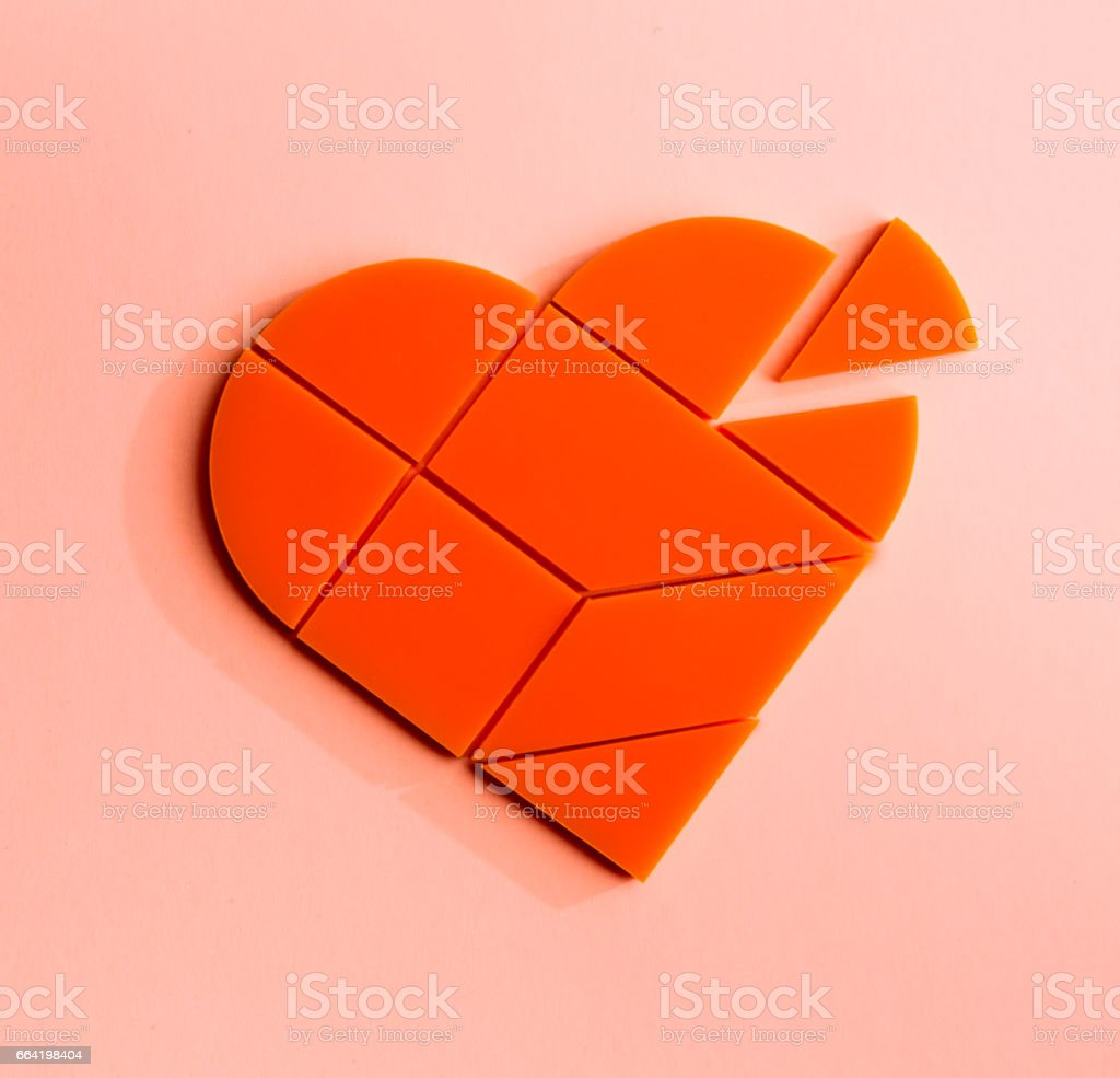 Plastic puzzle in the form of heart with disconnected piece on a pink background stock photo