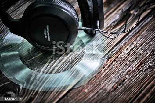Plastic records and headphones on wooden table