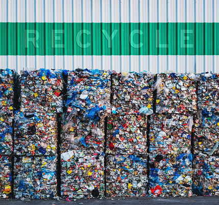 Large bundles of plastic bags, cans and milk containers await processing at a recycling center.  Added text above.