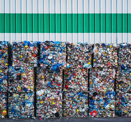 Large bundles of plastic bags, cans and milk containers await processing at a recycling center.