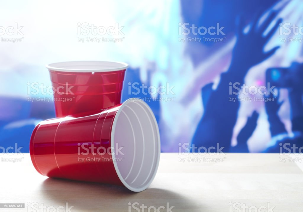 2 plastic red party cups on a table. One on its side. Nightclub or disco full of people dancing on the dance floor in the background. Perfect for marketing and promotion for events or college fest. stock photo