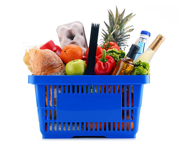 Plastic shopping basket with assorted grocery products Plastic shopping basket with assorted grocery products isolated on white shopping basket stock pictures, royalty-free photos & images