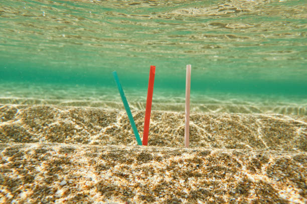 plastic single use straws in the ocean, staged image. - trash stock photos and pictures