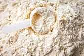 plastic spoon scoop in vanilla whey protein powder