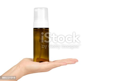istock Plastic spray bottle with pump in hand isolated on white background. Foam dispenser for face care. Container with body lotion. 885231916