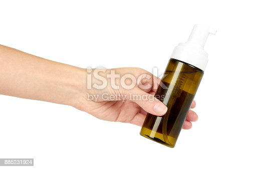 istock Plastic spray bottle with pump in hand isolated on white background. Foam dispenser for face care. Container with body lotion. 885231924