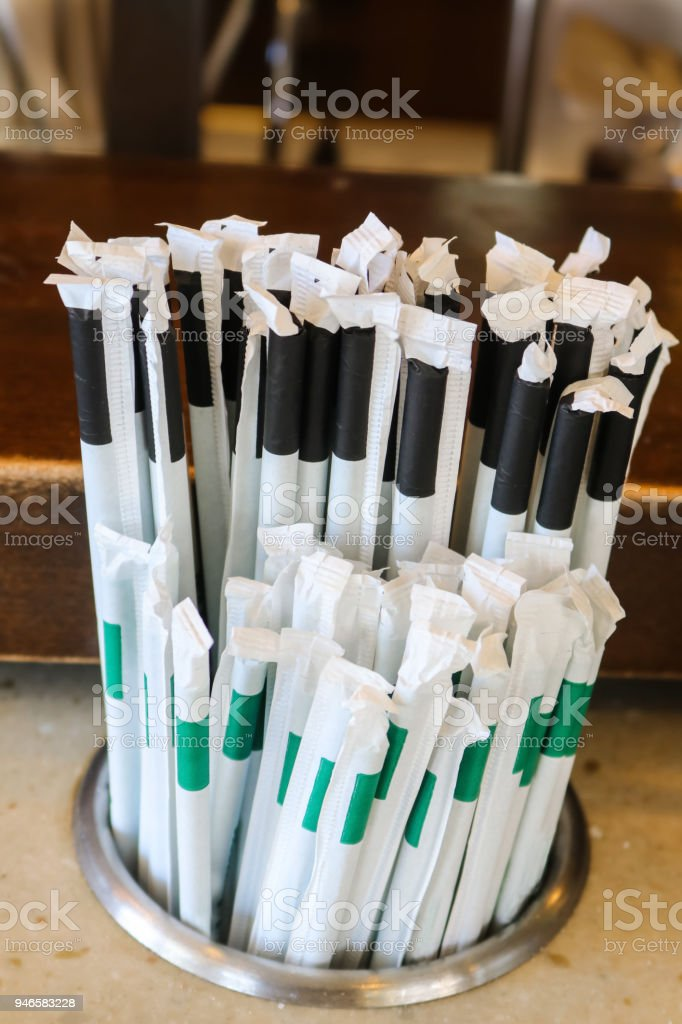 Plastic straws with paper wrappers in counter holder - the straws that many states and countries are outlawing but are still used many places stock photo