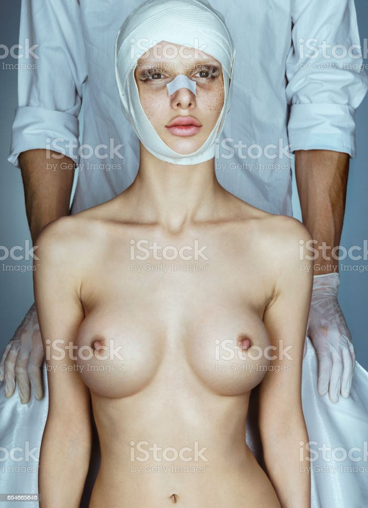 Plastic surgeon with patient after breast enlargement surgery. stock photo