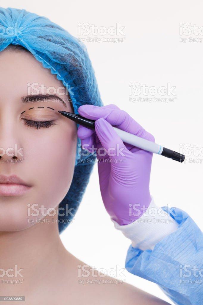 Plastische Chirurgie-Konzept. Arzt Zeichnung Markierungen auf weibliches Gesicht vor weißem Hintergrund – Foto