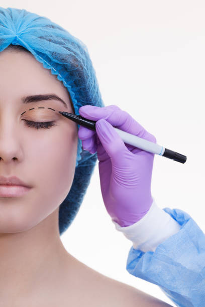 plastic surgery concept. doctor drawing marks on female face against white background - eyelid stock pictures, royalty-free photos & images