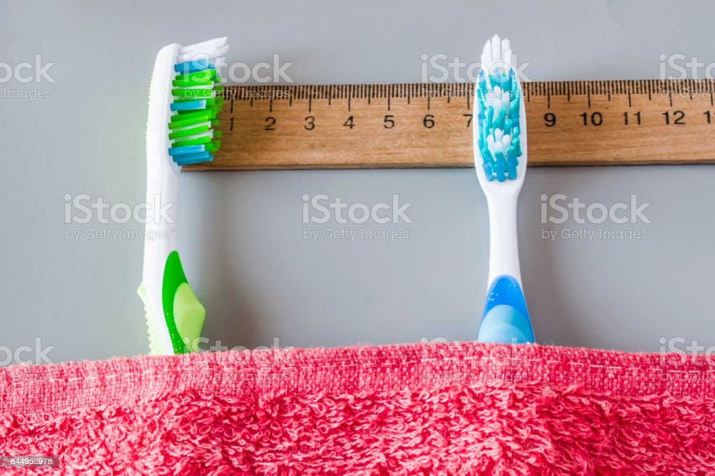 plastic toothbrushes lie on the ruler under the towel stock photo