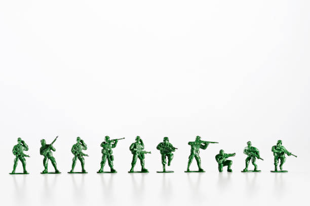Plastic toy soldiers are standing in a row on a white background stock photo